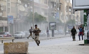 A member of the Libyan army runs with a weapon during clashes between members of Islamist militant group Ansar al-Sharia and a Libyan army special forces unit in Ras Obeida